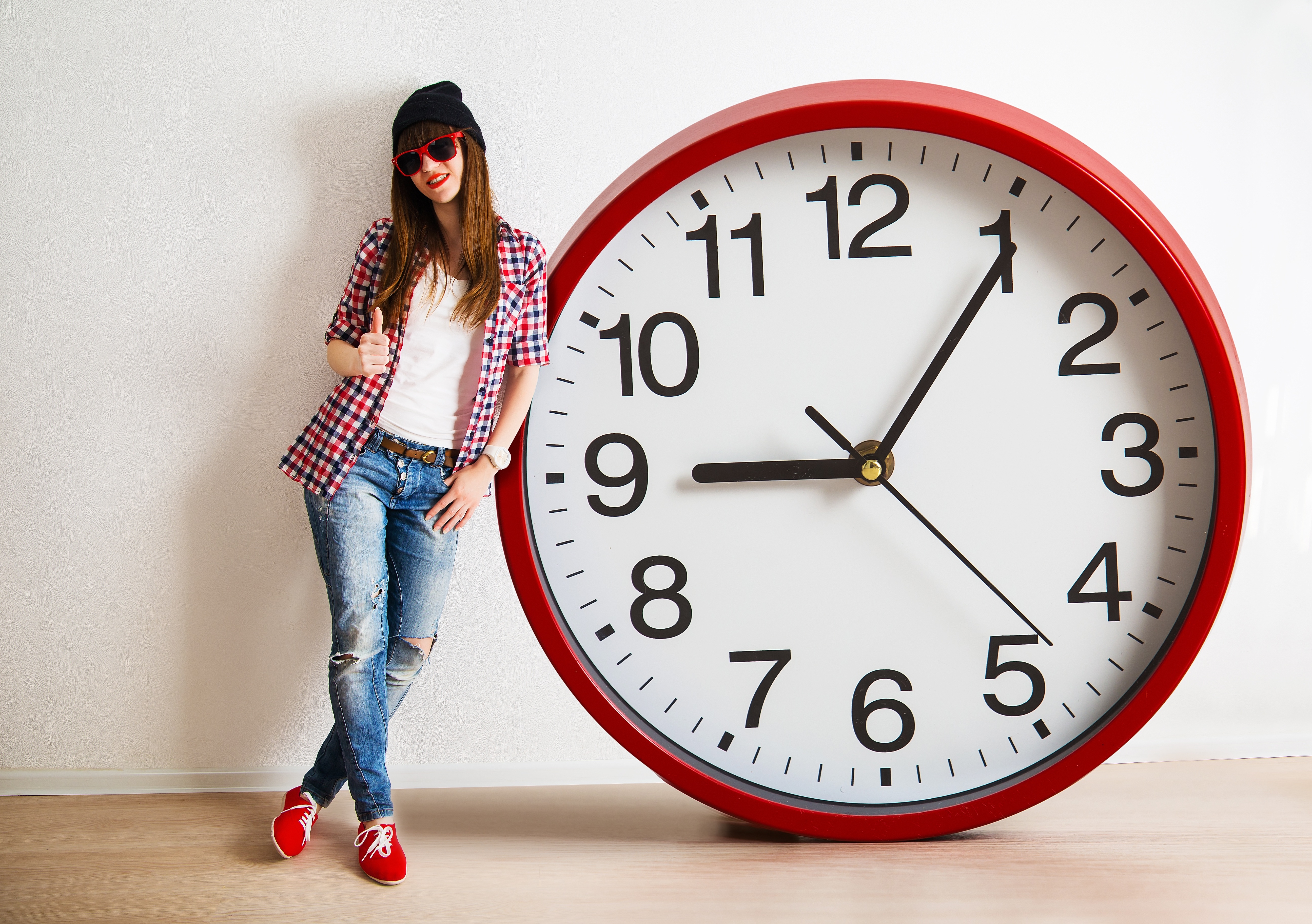 young woman with hat and glasses holding a clock. time managemen